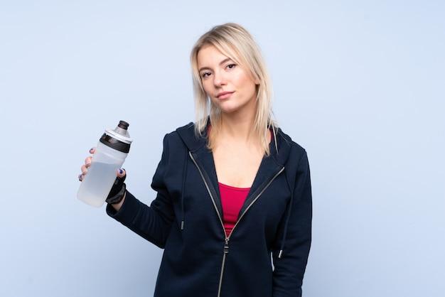 La giovane donna bionda di sport sopra il wallwith blu isolato mette in mostra la bottiglia di acqua