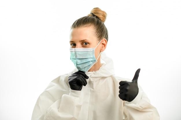 La giovane donna bionda in vestito protettivo e guanti che mostrano i pollici aumenta il segno