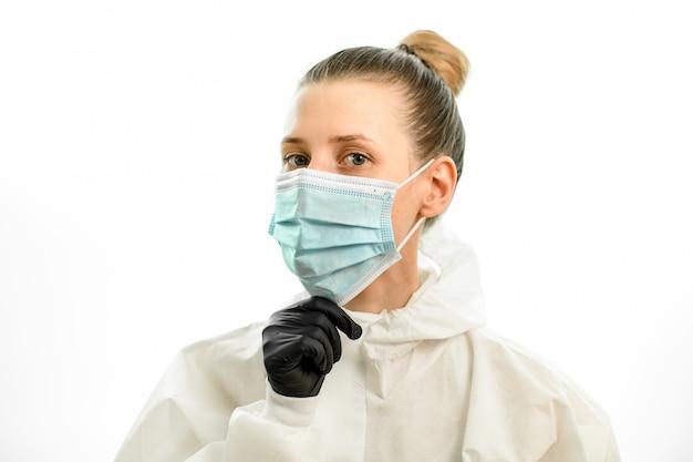 La giovane donna bionda regola la mascherina chirurgica sul suo fronte
