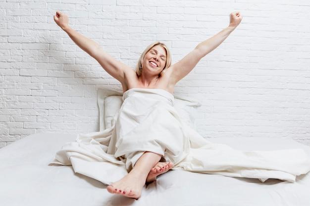 La giovane donna bionda si allunga a letto.