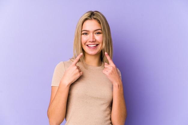 La giovane donna bionda sorride, indicando le dita alla bocca