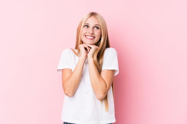 La giovane donna bionda su fondo rosa tiene le mani sotto il mento, sta guardando felicemente da parte.