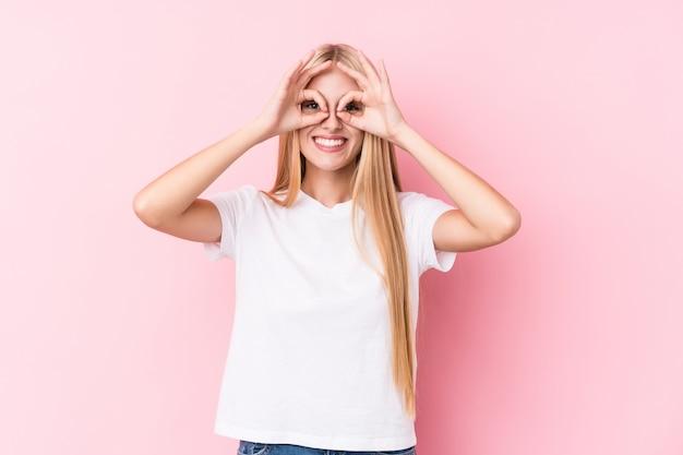 La giovane donna bionda sulla parete rosa che mostra bene firma sopra gli occhi