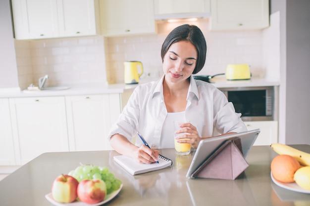 La giovane donna calma e pacifica si siede alla tavola e scrive in taccuino.