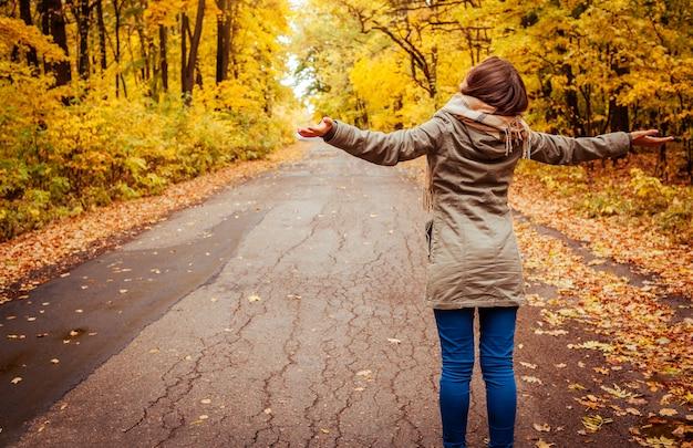 La giovane donna cammina nella foresta di autunno.