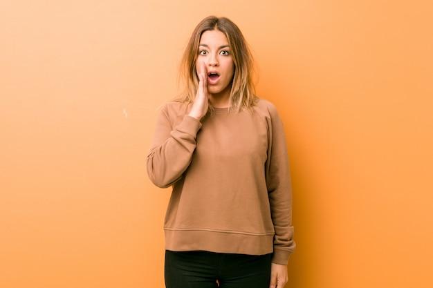 La giovane donna carismatica autentica contro un muro sta dicendo una notizia di frenata segreta e sta guardando da parte