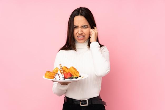 La giovane donna castana che tiene le cialde sopra la parete rosa ha frustrato e coprendo le orecchie