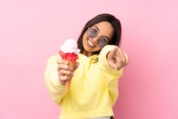 La giovane donna castana che tiene un gelato della cornetta indica il dito mentre sorride