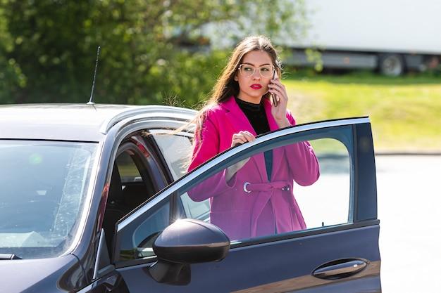 La giovane donna castana emozionale esce dall'auto e parla al telefono