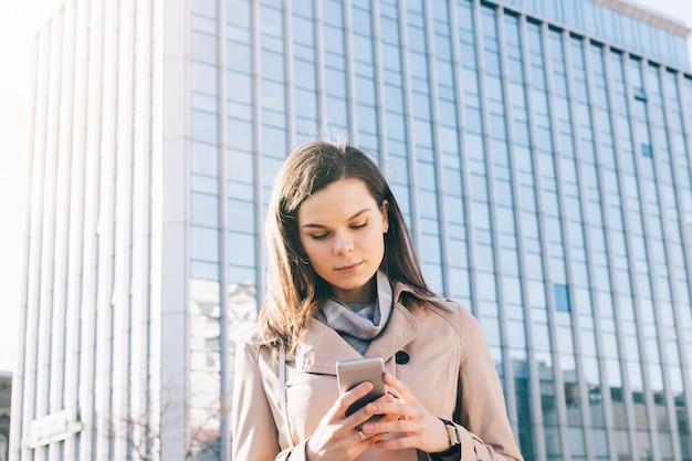 La giovane donna castana in cappotto beige esamina il telefono cellulare sul fondo del grattacielo