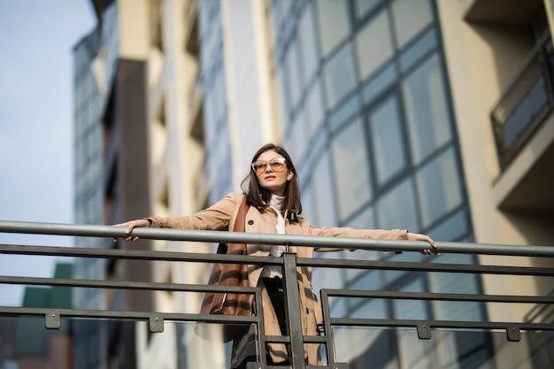La giovane donna castana in cappotto marrone chiaro gode degli ultimi giorni caldi di autunno