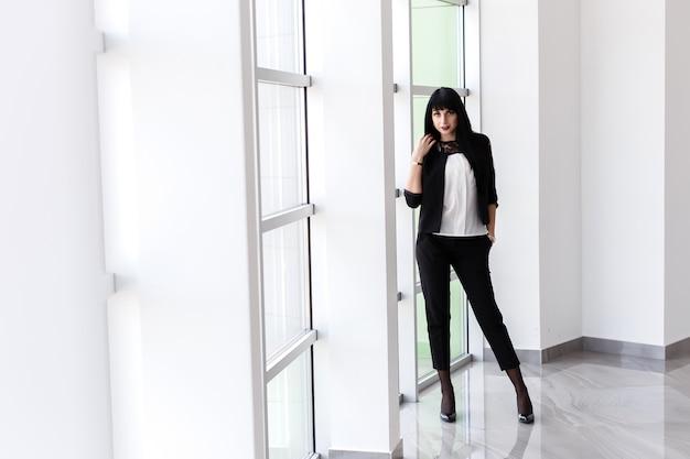 La giovane donna castana seria attraente si è vestita in un vestito nero che sta vicino alla finestra in ufficio, esaminante macchina fotografica.