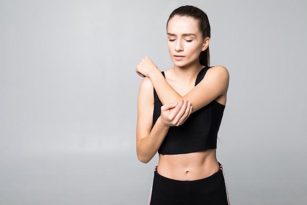 La giovane donna castana turbata ha ferito il braccio durante l'addestramento di sport, tocca il suo polso isolato sulla parete bianca