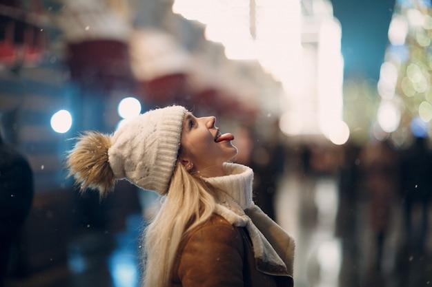 La giovane donna cattura i fiocchi di neve con la lingua della bocca