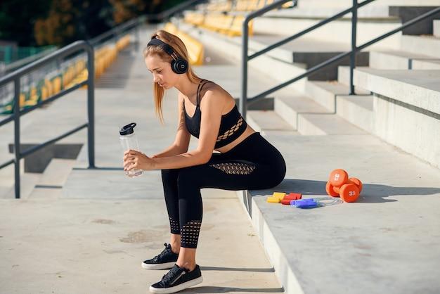 La giovane donna caucasica beve l'acqua e ascolta la musica dopo l'allenamento.