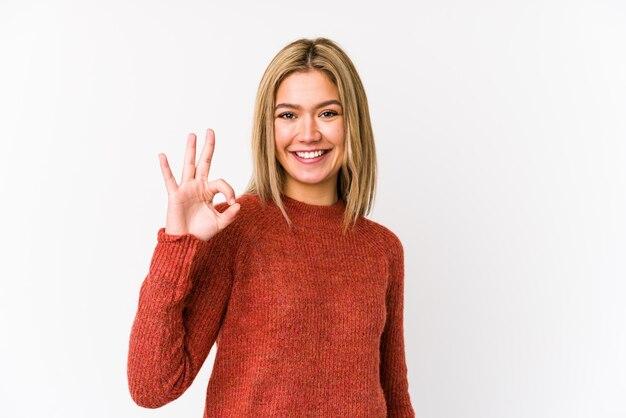 La giovane donna caucasica bionda ha isolato il gesto giusto di mostra allegro e sicuro.