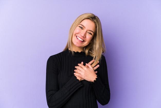La giovane donna caucasica bionda ha isolato la risata mantenendo le mani sul cuore, concetto di felicità.