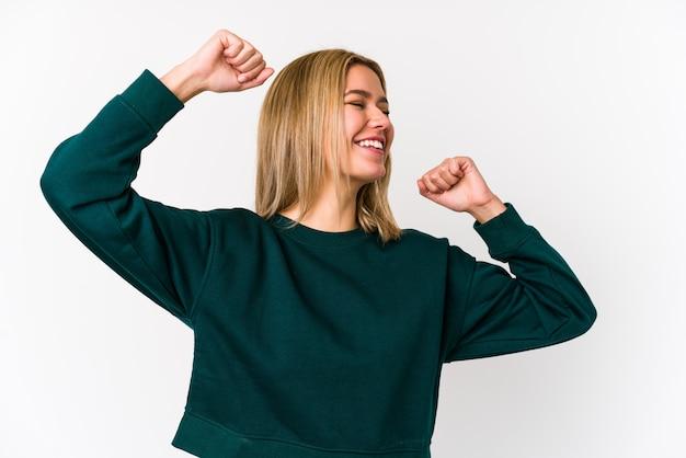 La giovane donna caucasica bionda isolata che celebra un giorno speciale, salta e alza le braccia con energia.