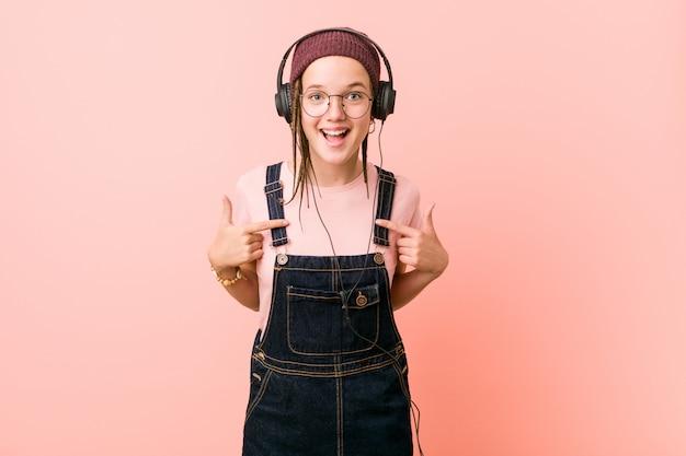 La giovane donna caucasica che ascolta la musica ha sorpreso indicando se stesso, sorridendo ampiamente.
