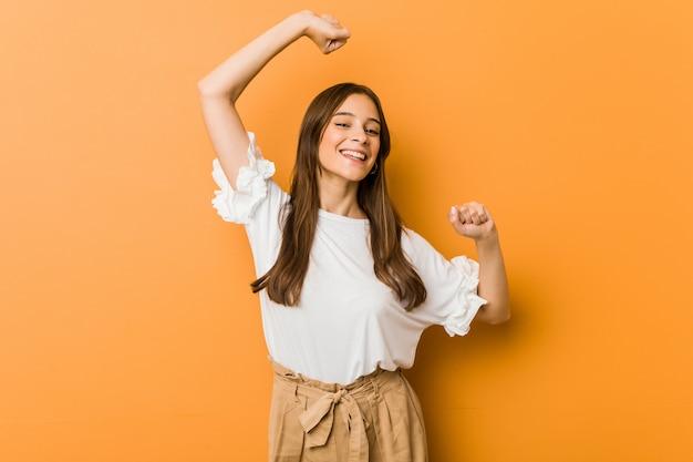 La giovane donna caucasica che celebra un giorno speciale, salta e alza le braccia con energia