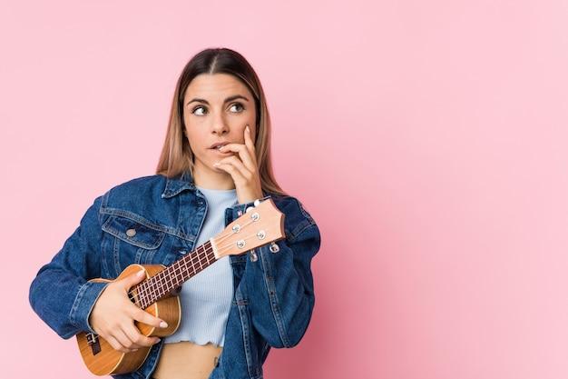 La giovane donna caucasica che gioca le ukelele si è distesa pensando a qualcosa che esamina uno spazio della copia.