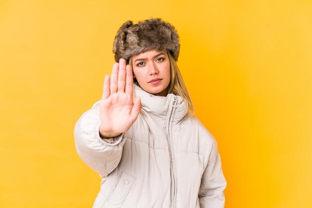 La giovane donna caucasica che indossa i vestiti dell'inverno ha isolato la condizione con il fanale di arresto di rappresentazione della mano tesa, impedendovi.