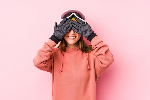 La giovane donna caucasica che indossa i vestiti di uno sci copre gli occhi di mani, sorride ampiamente aspettando una sorpresa.