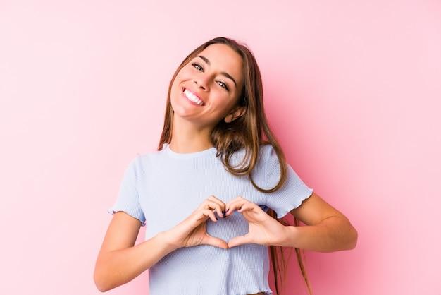 La giovane donna caucasica che indossa i vestiti di uno sci ha isolato sorridere e mostrare una forma del cuore con le mani.