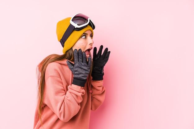 La giovane donna caucasica che indossa un abbigliamento da sci isolato grida forte, tiene gli occhi aperti e le mani tese.
