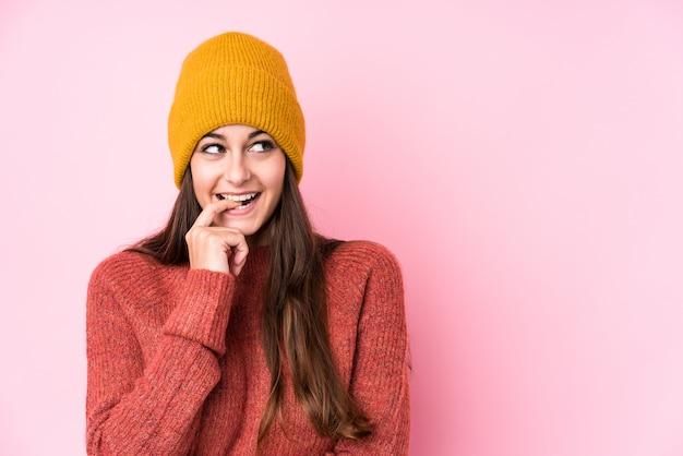 La giovane donna caucasica che indossa un cappuccio della lana si è distesa pensando a qualcosa che esamina uno spazio della copia.