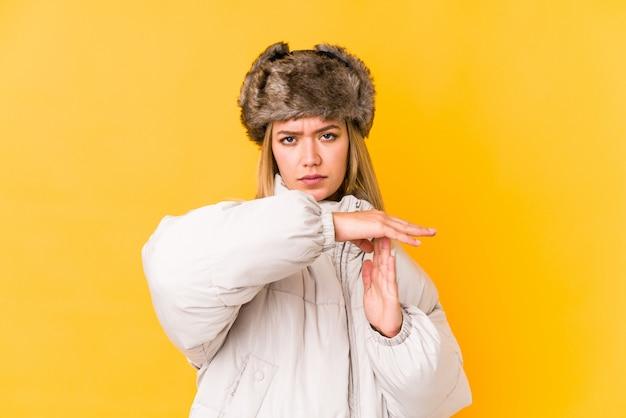 La giovane donna caucasica che indossa un inverno copre la mostra del gesto di prespegnimento.