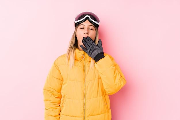 La giovane donna caucasica che indossa uno sci copre di una parete rosa che sbadiglia mostrando un gesto stanco che copre la bocca con la mano.