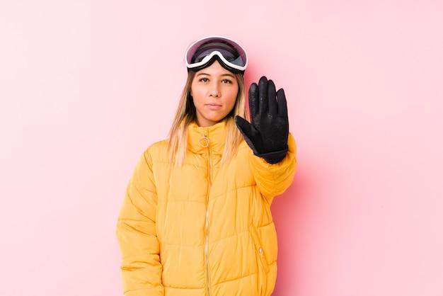 La giovane donna caucasica che indossa uno sci copre in una parete rosa che sta con il fanale di arresto di rappresentazione della mano tesa, impedendovi.