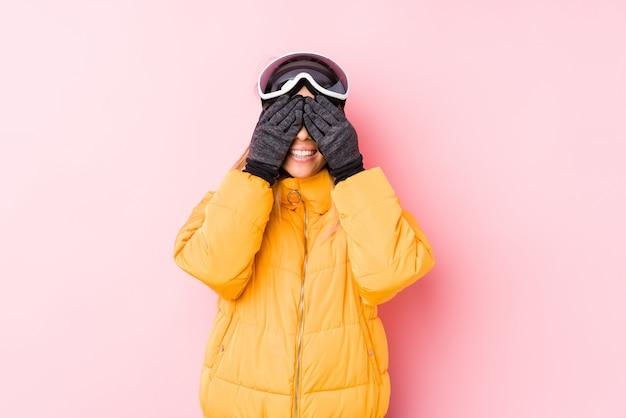 La giovane donna caucasica che indossa uno sci copre in una parete rosa copre gli occhi con le mani, sorride ampiamente aspettando una sorpresa.