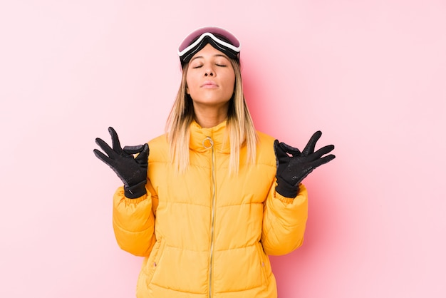 La giovane donna caucasica che indossa uno sci copre in una parete rosa si rilassa dopo una dura giornata di lavoro, sta eseguendo yoga.