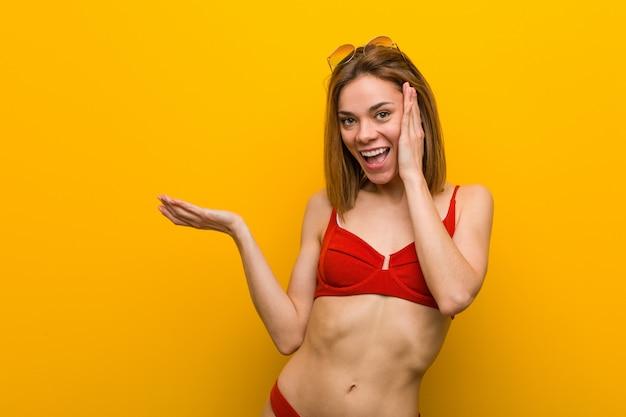 La giovane donna caucasica che porta lo spazio della copia del bikini e degli occhiali da sole tiene su una palma, tiene per mano la guancia