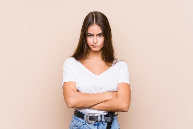La giovane donna caucasica che posa il fronte accigliato nel dispiacere, tiene le armi piegate.