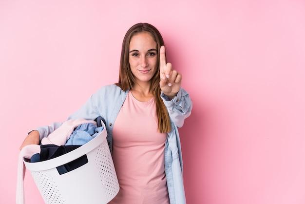 La giovane donna caucasica che prende i vestiti sporchi ha isolato la mostra del numero uno con il dito.