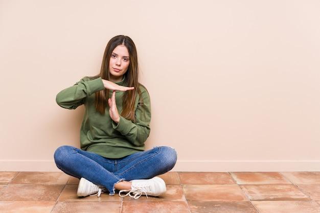 La giovane donna caucasica che si siede sul pavimento ha isolato la mostra del gesto di prespegnimento.