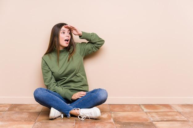 La giovane donna caucasica che si siede sul pavimento ha isolato lo sguardo lontano tenendo la mano sulla fronte.