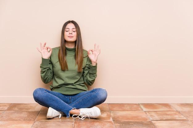 La giovane donna caucasica che si siede sul pavimento isolato si rilassa dopo la dura giornata lavorativa, sta eseguendo l'yoga.