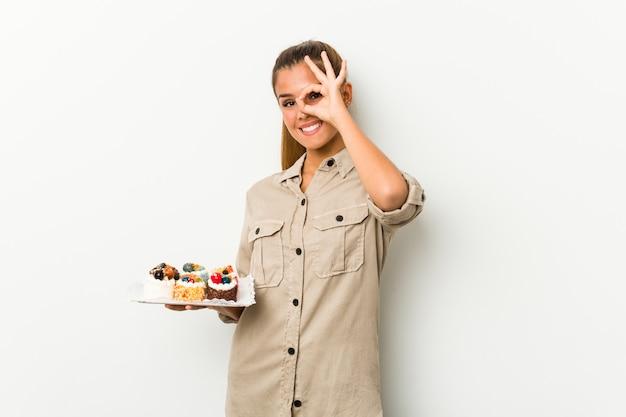 La giovane donna caucasica che tiene le torte dolci ha eccitato mantenendo il gesto giusto sull'occhio.