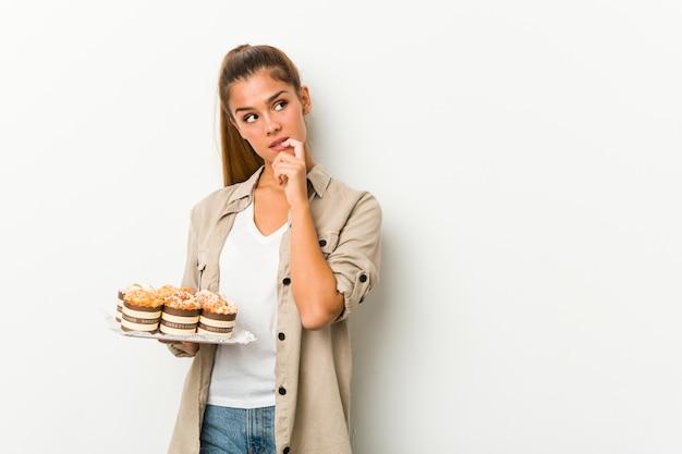 La giovane donna caucasica che tiene le torte dolci si è distesa pensando a qualcosa che esamina uno spazio della copia.