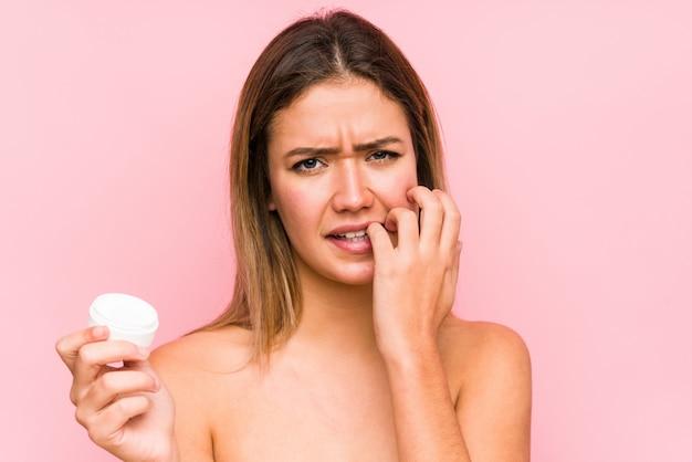 La giovane donna caucasica che tiene un idratante ha isolato le unghie mordaci, nervose e molto ansiose.