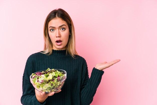 La giovane donna caucasica che tiene un'insalata ha impressionato la tenuta dello spazio in bianco sulla palma.