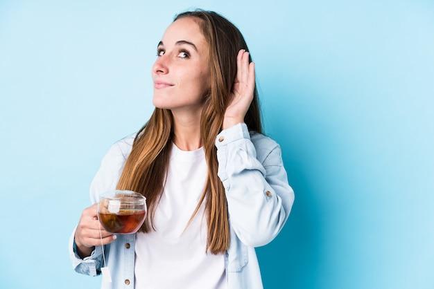 La giovane donna caucasica che tiene un tè ha isolato la prova di ascoltare un gossip.
