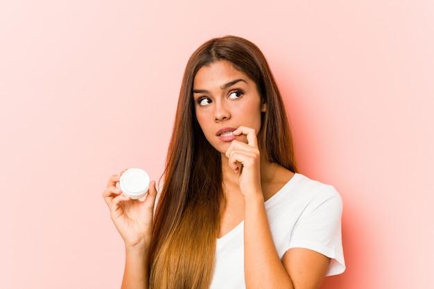 La giovane donna caucasica che tiene una crema idratante si è distesa pensando a qualcosa che esamina uno spazio della copia.