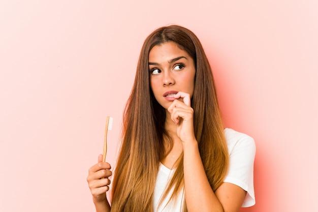 La giovane donna caucasica che tiene uno spazzolino da denti si è distesa pensando a qualcosa che esamina uno spazio.