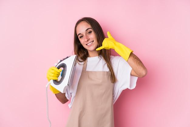 La giovane donna caucasica con il ferro da stiro ha isolato mostrando un gesto di chiamata di telefono cellulare con le dita.