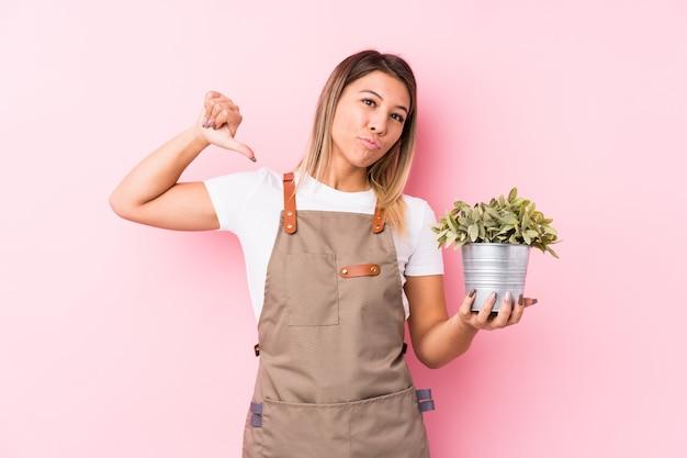 La giovane donna caucasica del giardiniere isolata si sente orgogliosa e sicura di sé, esempio da seguire.